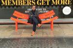 """Der Buchautor und Redner Dr. Peter Spork sitzt auf einer oragnegnen und gebogenen Bank. Hinter ihm steht """"members get more""""."""