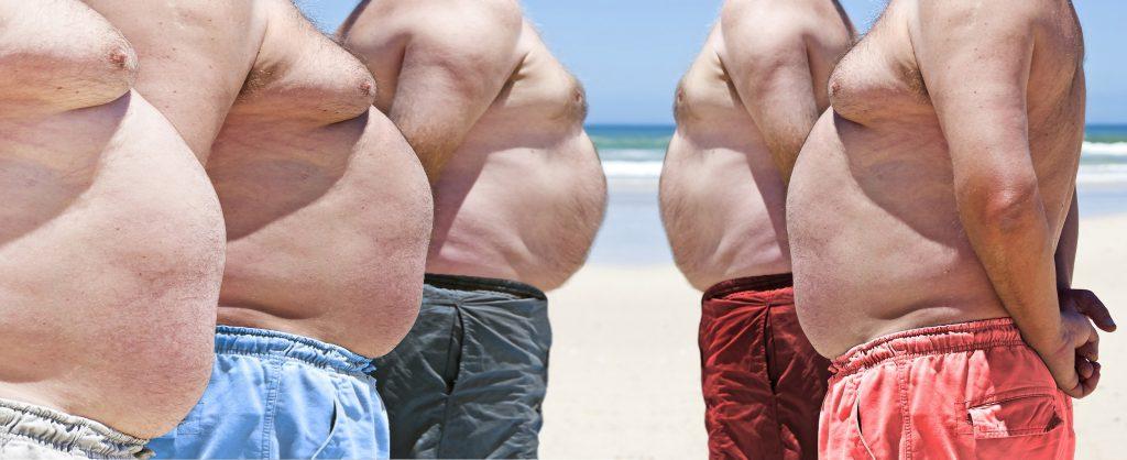 Fünf stark übergewichtige Männer an einem Strand. Die Oberkörper sind nackt.