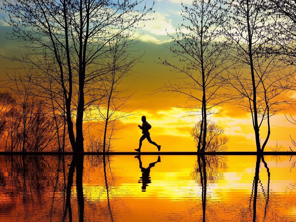 Man joggt vor Abendhimmel
